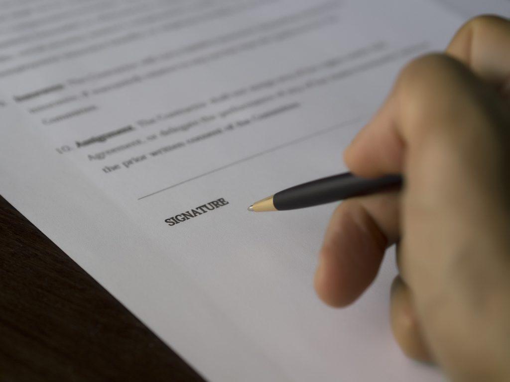 Une main qui va signer un acte d'huissier