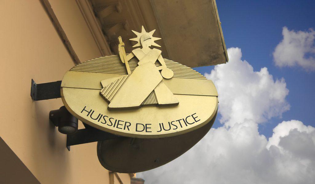 Un symbole huissier de justice or sur un mur jaune