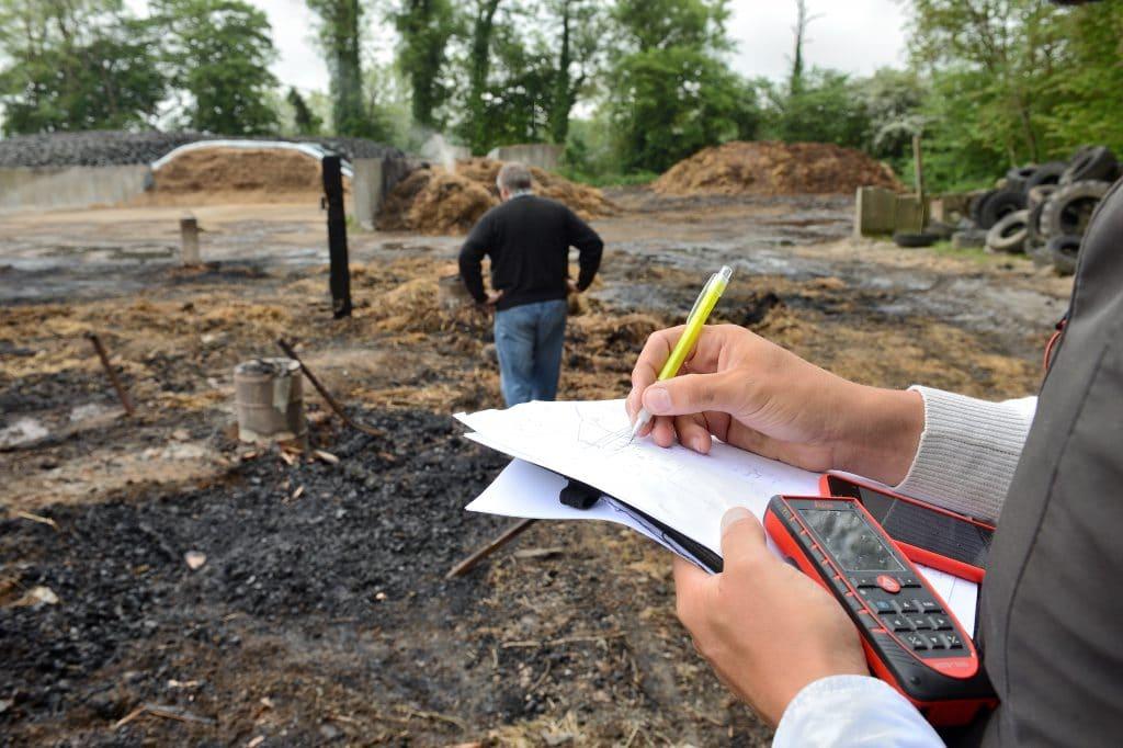 Un homme qui écrit et constate les dégâts sur un chantier