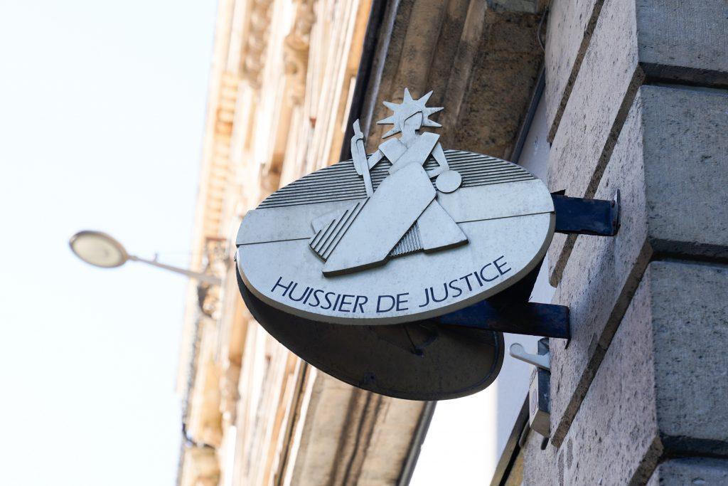 Un symbole gris Huissier de justice sur un mur en béton